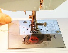 holding upper thread while threading a sewing machine